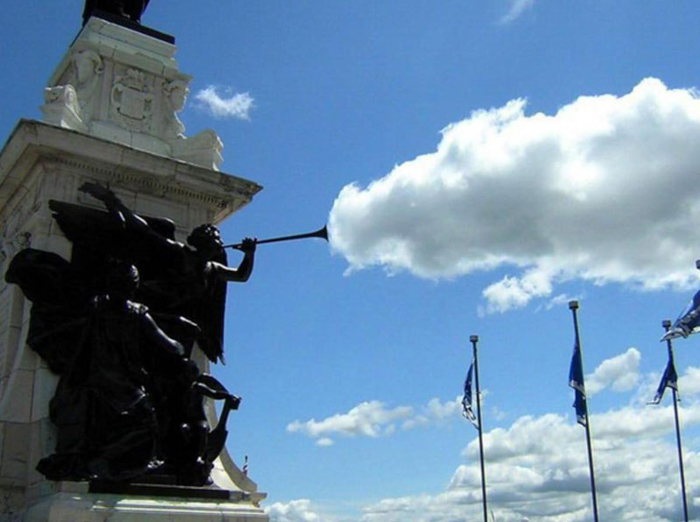 Photo of a statue with clouds in the background