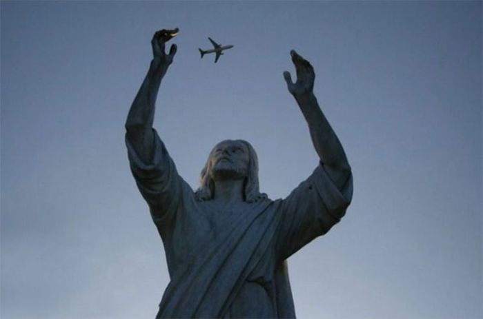 Photo of a Jesus statue with a plane above him