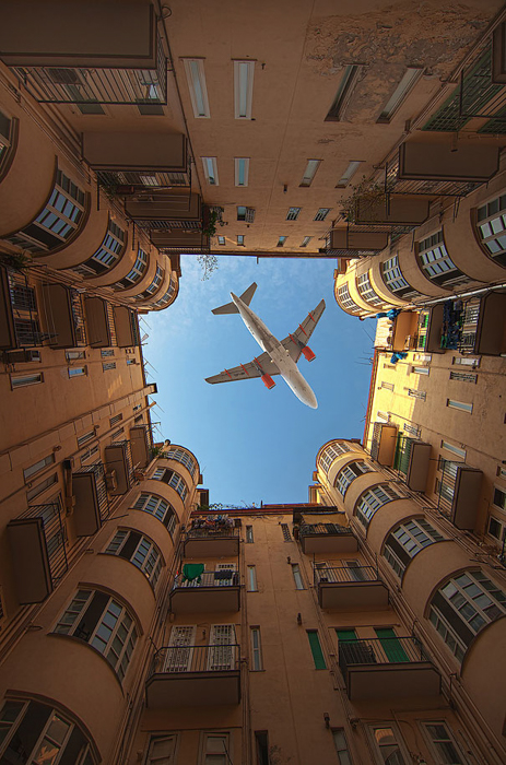 Photo of a plane flying above the middle of a courtyard