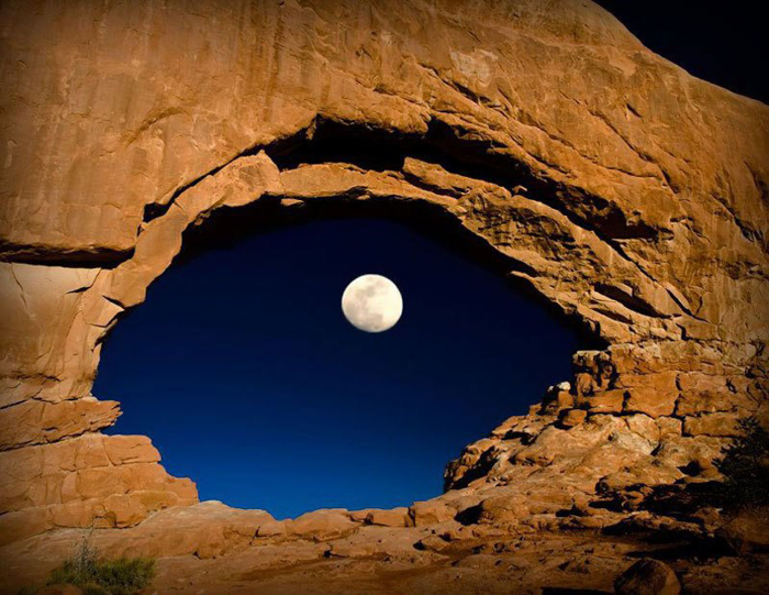 Photo of a cave with the moon appearing in a hole in the middle