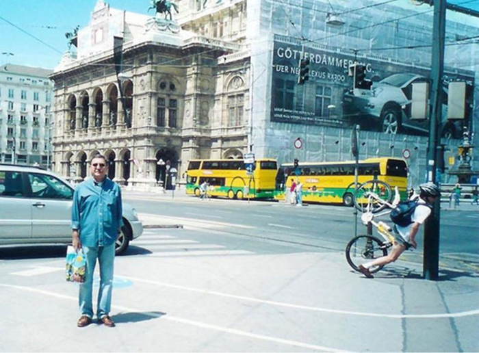 Tourist photo of a man standing on the street and a guy hitting a lamppost