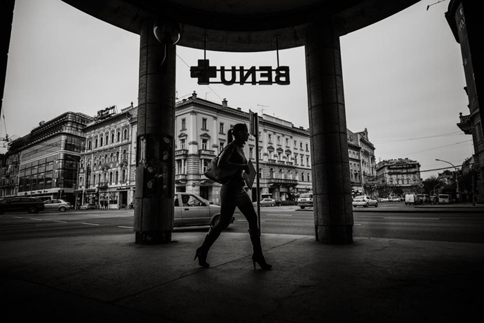 Black and white photo of a woman walking on the street