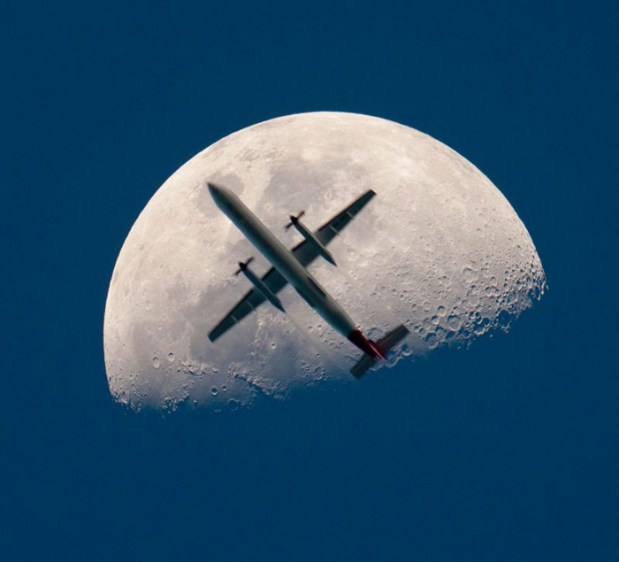 Photo of a plane flying in front of the moon
