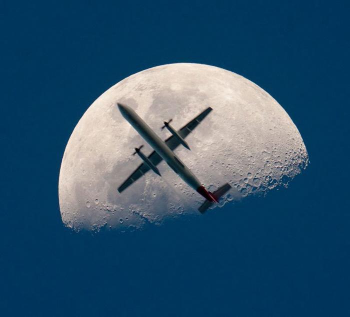 Foto de un avión volando frente a la luna.