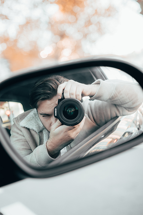 Reflection in a car wing mirror showing a man holding a camera