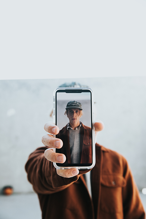A man holding a camera phone with his self portrait on the screen