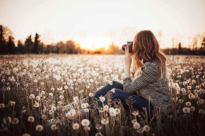 Girl in a field taking a photo of the landscape