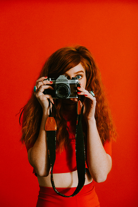 Red haired girl in front of a bright red screen holding a Pentax camera