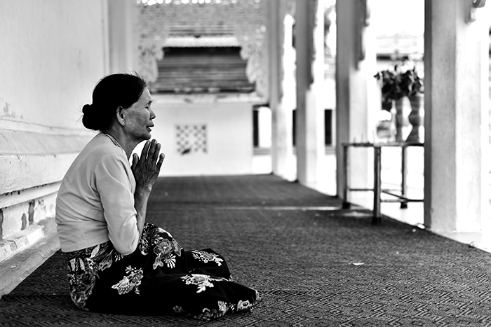 Black and white photo of a woman praying