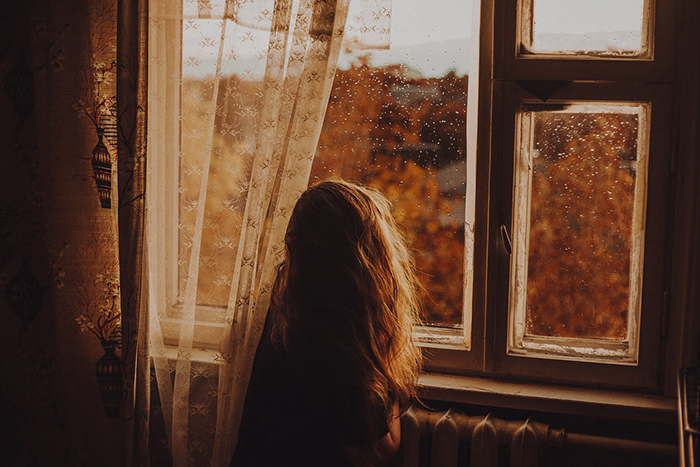 Photo of a woman looking out of a window on a rainy day