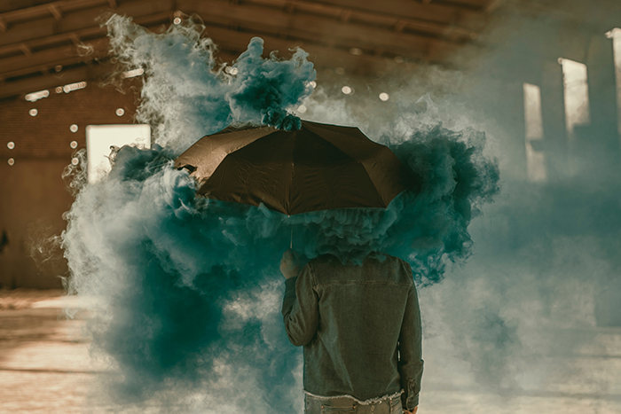Surreal photo of a person standing with an umbrella with the use of a green smoke bomb