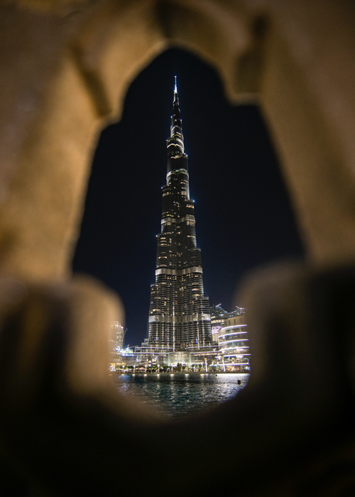Photo of a skyscraper at night shot through a hole