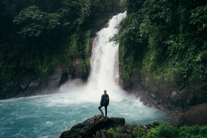 Photo of a man standing in front of a waterfall