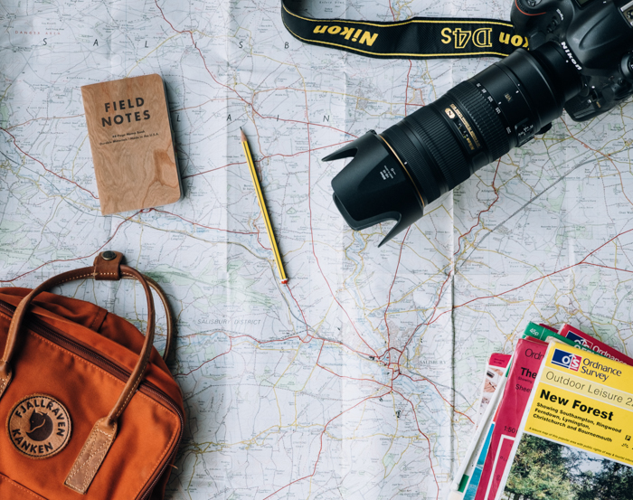 Photo of a camera, a map, a backpack and a notepad