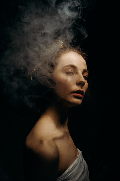 A moody portrait of a girl, with smoke used to create a dramatic effect