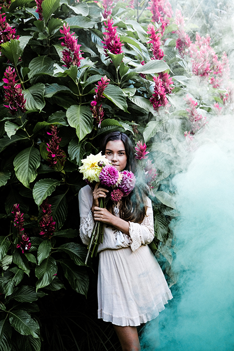 A girl standing and holding flowers, a large billow of smoke is coming towards her from the right hand side