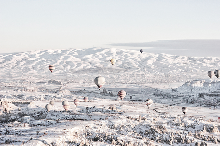 Hit air balloons floating over a snowy landscape