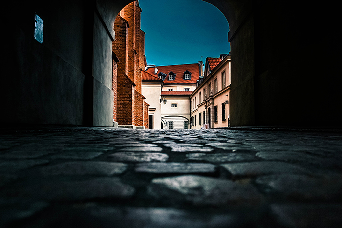 An archway over a cobbled street shot from a low angle