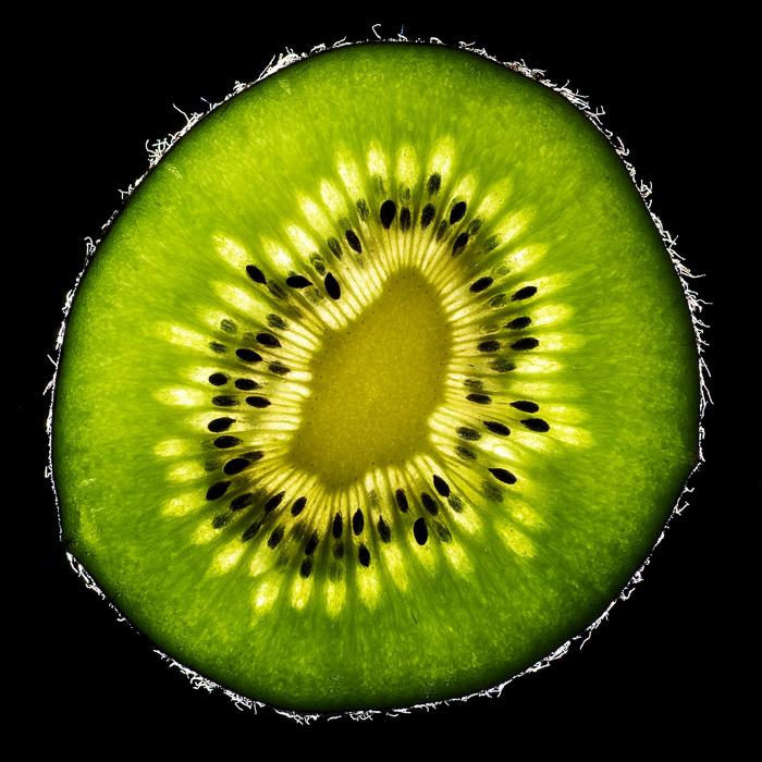 unique photo of a slice of kiwi against black background