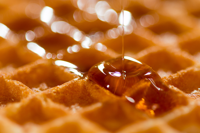 close up photo of honey pouring on a waffle
