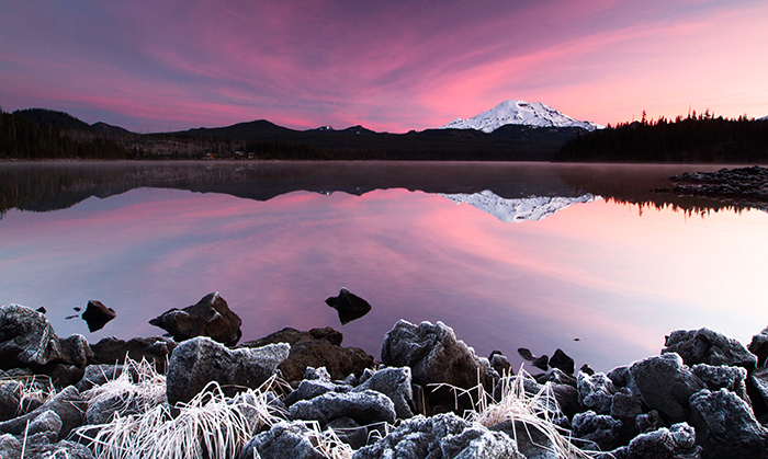 Landscape photo of a snowy mountain at sunset in purple hues