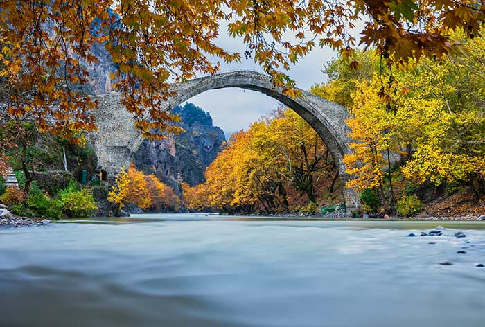 A bridge over a river with autumnal trees on the shore