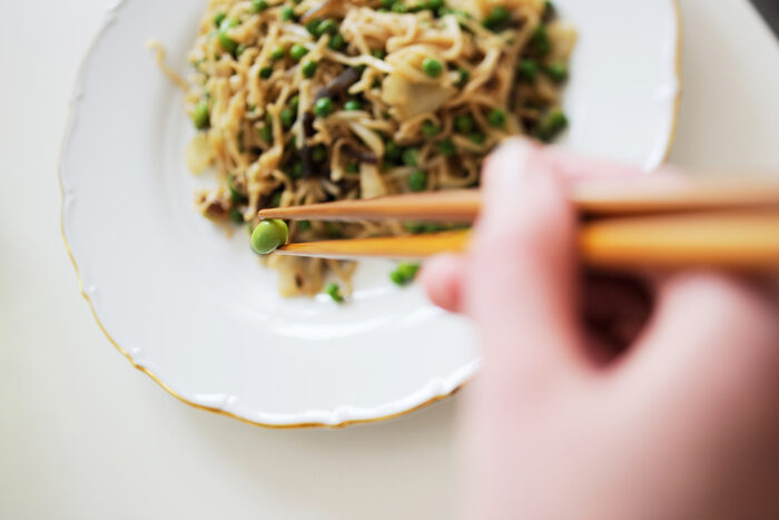 Photo of a plate of noodles and a hand holding chopsticks