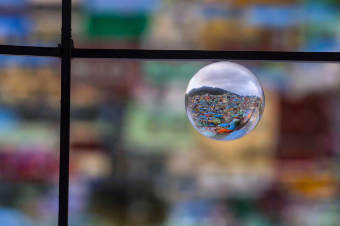 a crystal ball in a window frame reflecting a sprawling cityscape