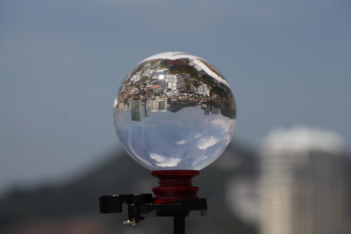 a lensball on a tripod, reflecting a sprawling cityscape
