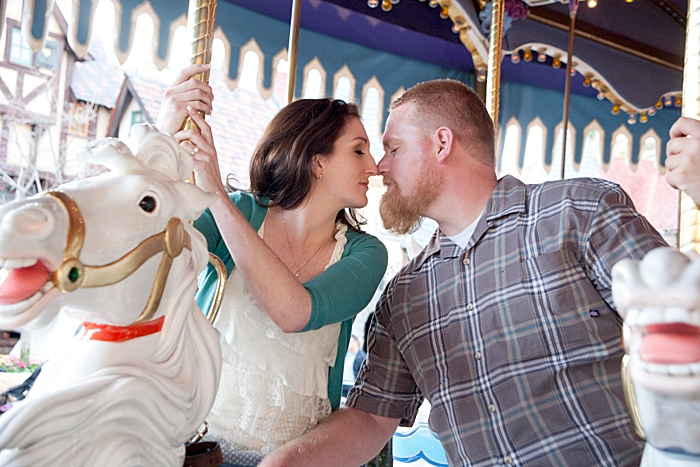 a romantic portrait of a couple kissing on a carousel