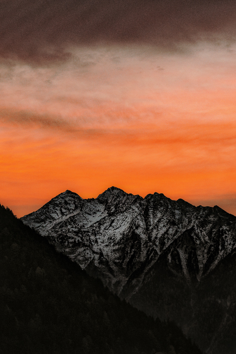 Photo of a mountain range at sunset with orange colours