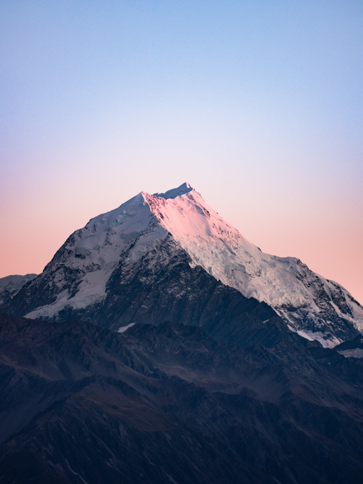 Photo of a snowy mountain peak at dawn