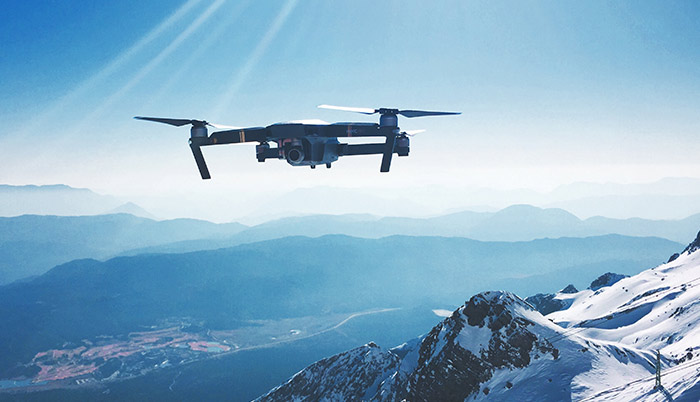 A drone flying above snowy mountains