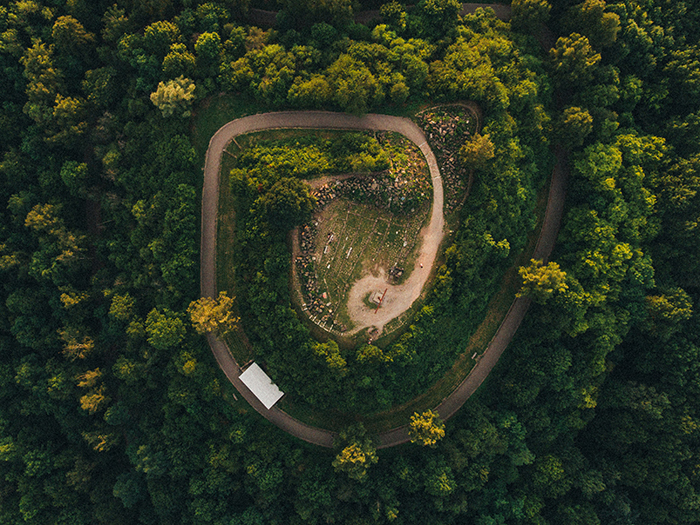 A drone photo of a forest and a spiral-like road