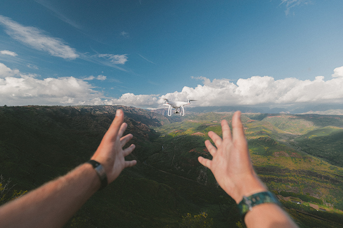 A photo of hands letting go of a flying drone