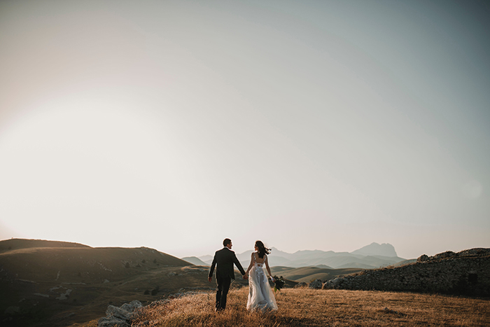 Drone wedding photo of a couple on a hill at sunset