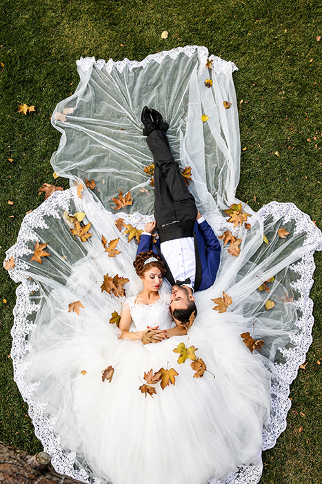 Drone wedding photo of the couple lying in the grass