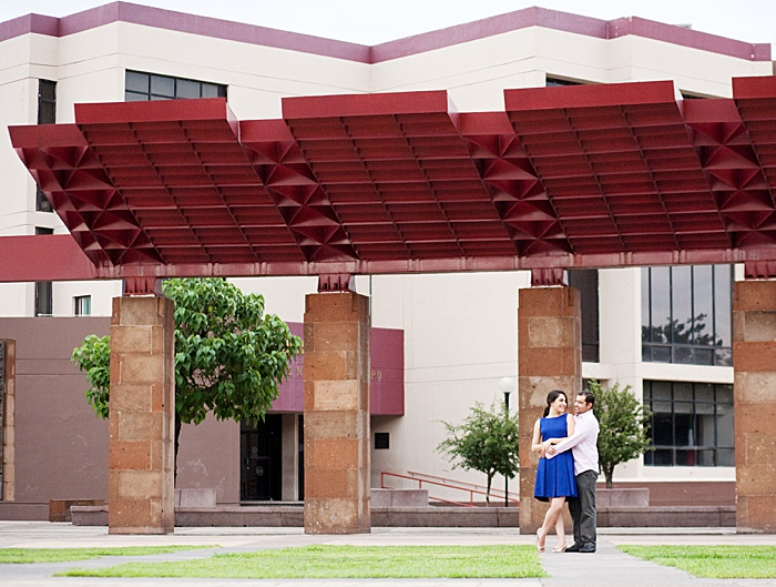 Couple hugging in front of a building for an engagement photo session