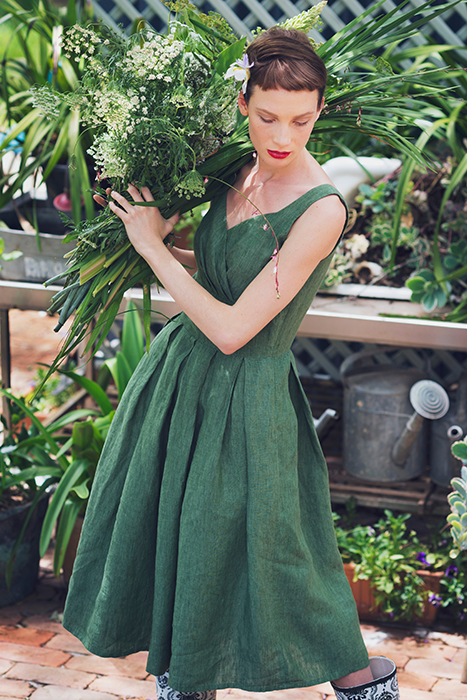 Photo of a model dressed in green holding plants