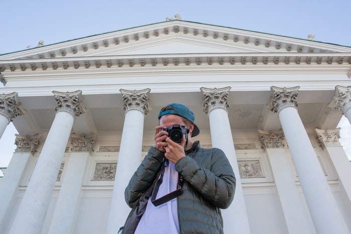Man holding camera in front of a large columned building