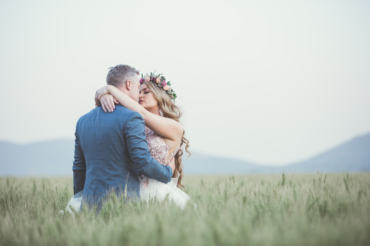 A wedding photography shot of a bride and groom in a field