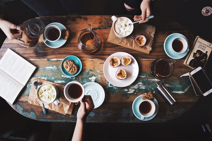 Coffee cups and food laid out on a wooden table