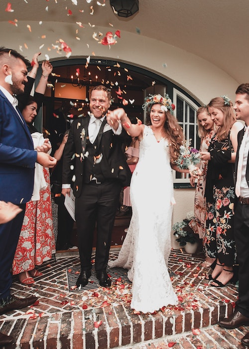 A shot of a bride and groom leaving the ceremony, with confetti in the air