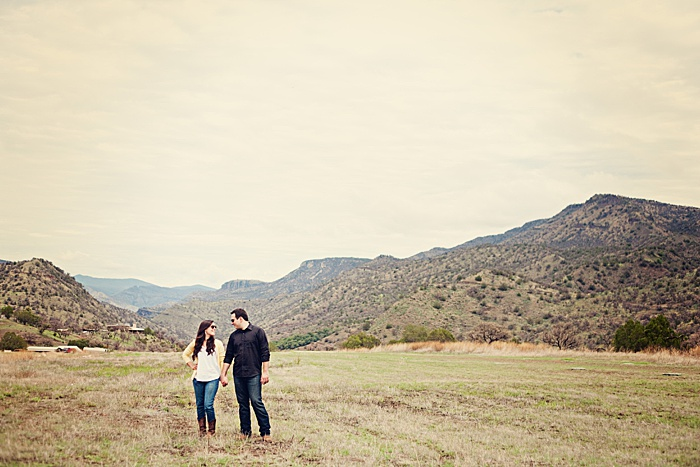 a romantic portrait of a couple trying engagement photo poses in a scenic landscape