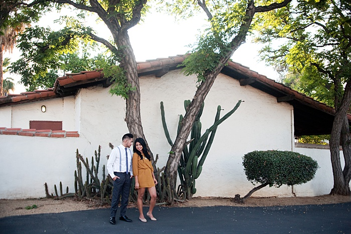 Young couple standing in front of a building with cacti
