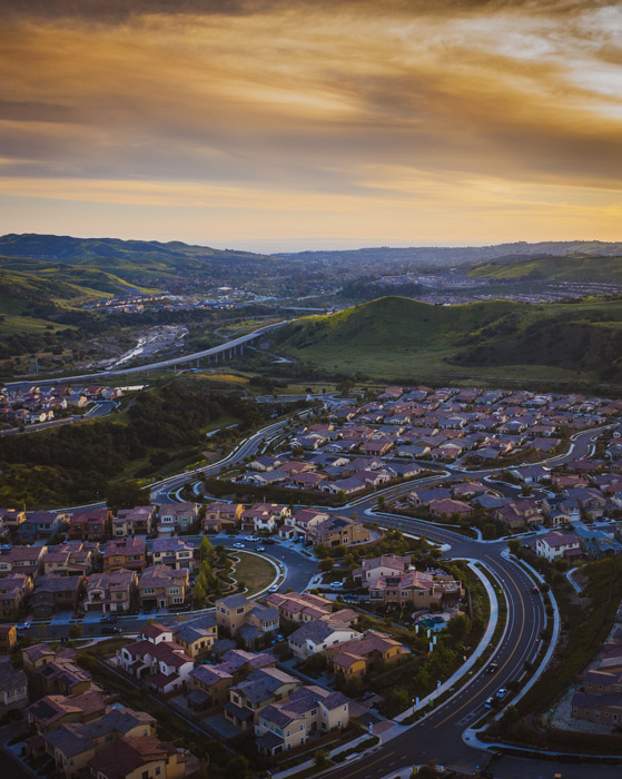 Drone photo of a city with hills at sunset