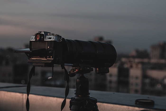 a telephoto lens on a tripod on the edge of a city rooftop