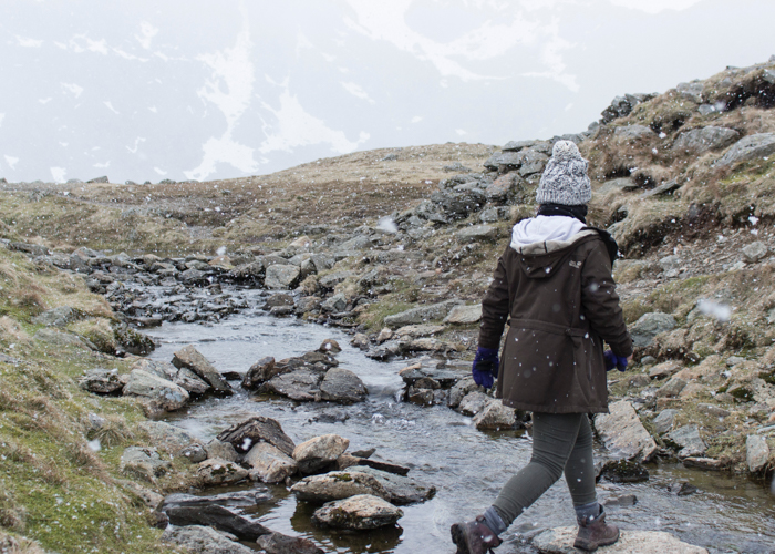 a photographer walking over a countryside stream