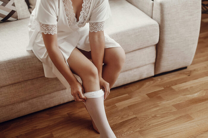 Boudoir photo of a woman taking off her tights