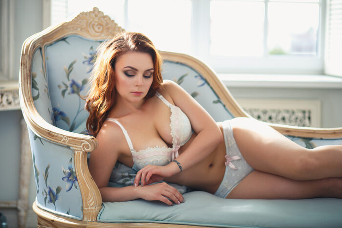 Boudoir photo of a woman posing on an armchair in lingerie
